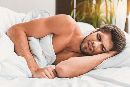 suffering: Bad dream. Man is lying in bed and sleeping. He frowning with closed eyes