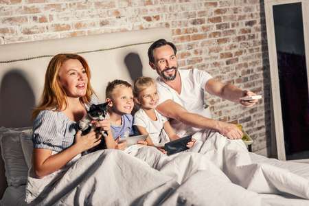 Lets start watching. Smiling father holding TV remote control. Children sitting in bed next to their parents and keeping digital tablets in hands while mother with cat beside them