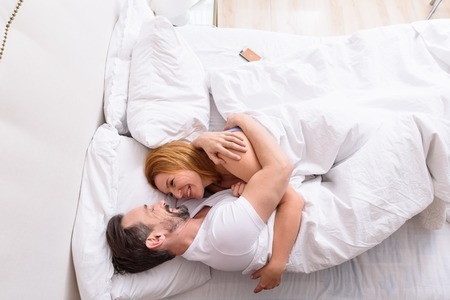 sexual relations: Our morning together is always the best time. Top view of mature couple relaxing on bed in morning, embracing and smiling