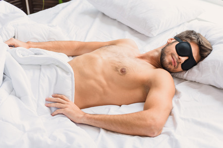 slumber: Calm young man is sleeping in bed with relaxation. His eyes are covered by eyewear Stock Photo