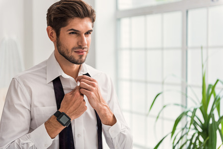 Self-confident young man is preparing for business meeting. He is wearing clothing at home
