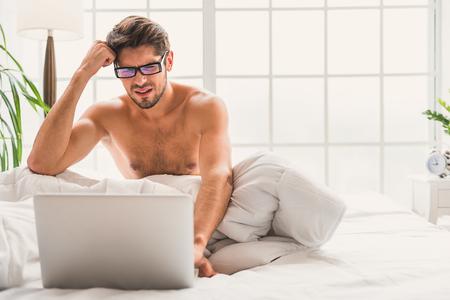desilusion: Tengo mucho trabajo. joven confundido está buscando en la computadora portátil con la decepción. Está sentado en la cama en su casa