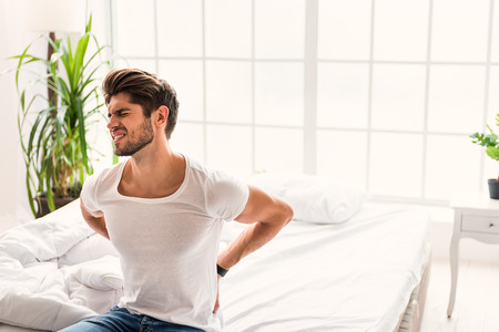 Young man suffering from backache. He is sitting on bed and touching body with frustration Stock Photo