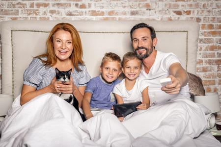 Wij willen deze show. Lachende ouders en kinderen televisie kijken, zitten in bed. Mooie moeder die kat in haar handen Stockfoto