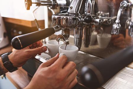 liquid espresso pouring into cups from portafilter, close up of barista hands