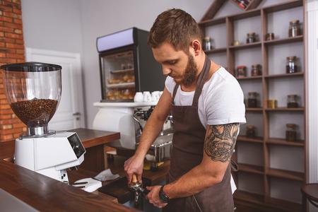 改ざんを使用してコーヒー豆を押すハンサムなバリスタのひげを生やした