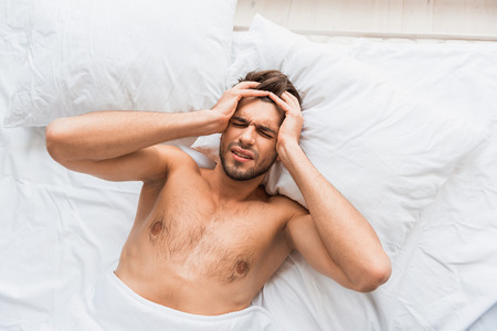 desperation: Young man is suffering from headache in bed. His eyes are closed with desperation