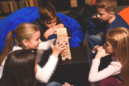 erudition: Group of cheerful children are playing board game