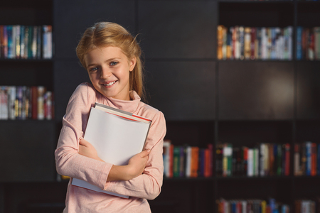 volumes: Smiling girl standing in front of shelves with volumes Stock Photo