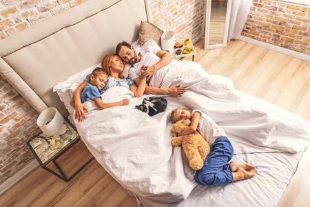 ママとパパの近くにあります。親と昼寝を取る 2 人の若い子供の平面図です。横に横になっている猫 写真素材