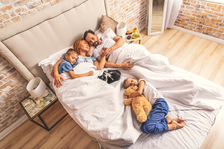 Be close to mommy and daddy. Top view of adult parents and their two young children taking nap. cat lying next to them