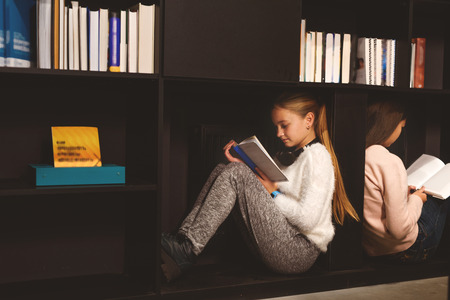 bookish: Two fascinated girls are sitting on shelves with open volumes Stock Photo