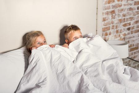 Horrorfilm. Scared kleine kinderen verstopt achter witte deken tijdens het kijken verschrikkelijk verhaal op tv