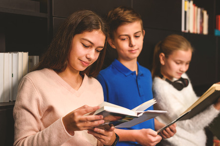 bookish: Group of children are standng near bookcase. Girls reading, boy is holding tab and looking at volume with interest