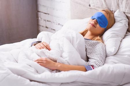 ベッドで夢を楽しむ穏やかな女の子。彼女は眼鏡と横たわっています。