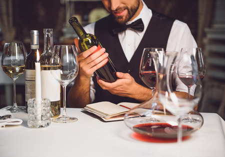 Softly smiling man is sitting at table and carrying bottle of crimson nectar Stock Photo