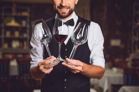 매혹 된 남자는 동시에 약간의 안경을 들고있다. 한 술잔이 스 칼레 와인으로 반으로 가득합니다.