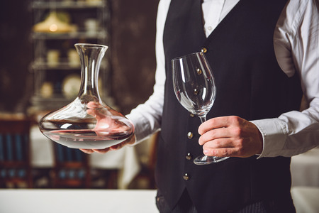Waiter is standing in room. He holding carafe full of nectar in one hand and empty glasswine in another