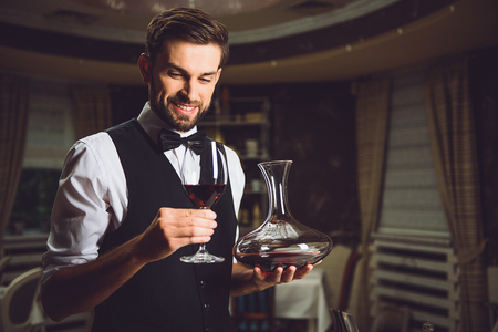 Smiling sommelier is holding carafe and glass with scarlet beverage Stock Photo