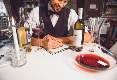 restaurant questions: Smiling man is sitting at table and writing wine critics