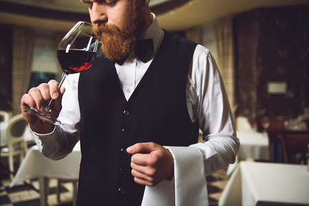 Sommelier is staying, taking glass with scarlet nectar and smelling it. His eyes are closed in thoughtfulness Stock Photo