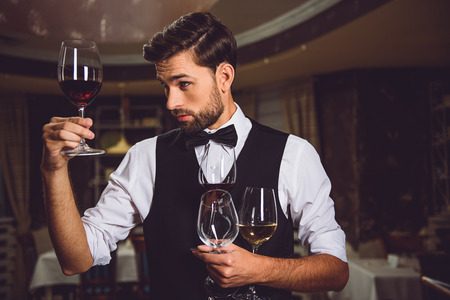 Attentive man is staying in room, holding few glasses. He fixedly gazing at goblet with crimson wine
