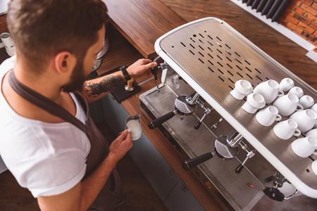 camarero de celebración de una jarra con leche frente a la máquina de café, de alto ángulo photo