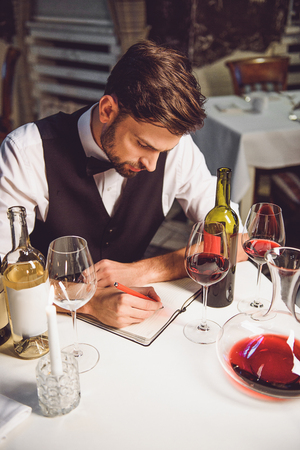 hardly: Sommelier is sitting neat table, hardly composing recall in notebook among variety of white and crimson nectar