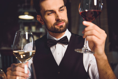 Man is sitting near table and holding wineglasses with drink. He looking at beverage with attention