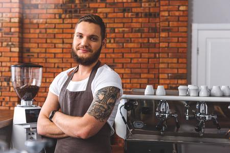 나는 직업이 좋아. 행복 한 젊은 바리 커피 기계 근처에 서 있고 포즈. 그는 카메라를보고 웃 고있다 photo
