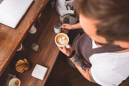 kopje koffie kunst met de vorm van een hart in handen van cafe werknemer, hoge hoek photo