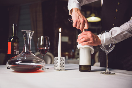 Waiter is holding flask with napkin and make it unclosed. Scarlet wine on table Stock Photo