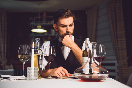 critic: Attentive wine critic is sitting near table and tensely thinking about his recall Stock Photo