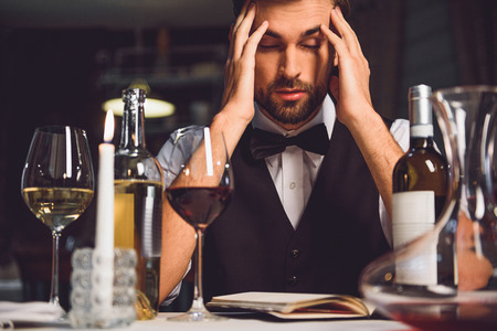 hardly: Puzzled man is sitting near table and touching his head with fingers. He hardly thinking. Focus on wine Stock Photo