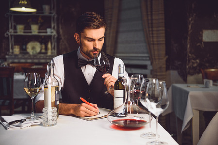 Professional sommelier smelling red drink from wineglass with pleasure Stock Photo