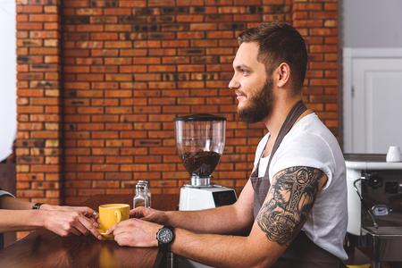 Vrolijke mannelijke barman serveert cliënt in koffiehuis. Hij staat en houdt beker photo