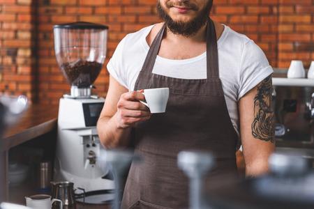 Ayudarse a sí mismo con la taza de café. barista Alegre está de pie en la cocina con la bebida caliente photo