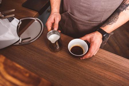 Vista superior cerca de las manos del barista haciendo café con leche en la cafetería. Él está de pie en la barra y sosteniendo la jarra de leche y taza de café photo