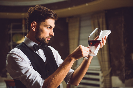 critic: Liquor critic is taking wineglass with red nectar on white napkin and looking attentively Stock Photo