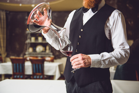 Bearded waiter is pouring ruby beverage from carafe into fragile goblet