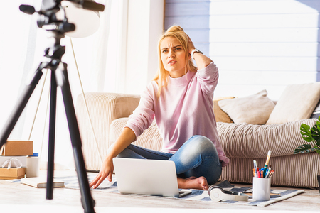 desilusion: mujer joven desconcertado es la grabación de vídeo para el blog como en casa. Ella está sentada y mirando a la cámara con aire pensativo. Señora toca la cabeza con decepción Foto de archivo