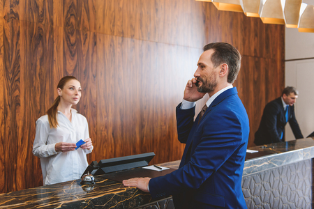 cardkey: I arrived, everything is fine. Mature businessman talking on smart phone and waiting for registration. Female receptionist holding cardkey and looking at him