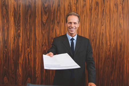 You must fill out form. Smiling male mature receptionist standing behind counter and giving documents for signature