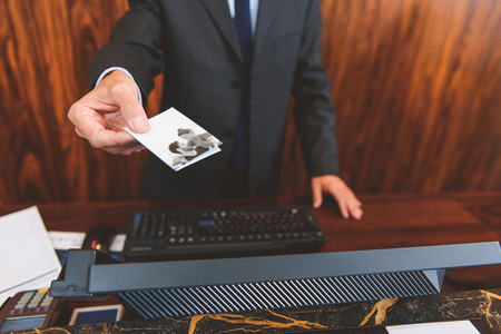 cardkey: Here is a key. Close up of male receptionist giving cardkey to customer while standing at reception