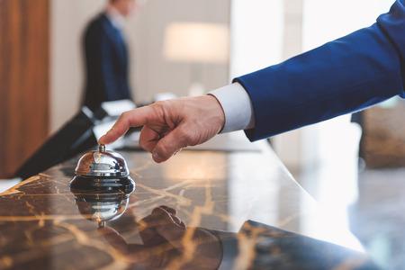 Check-in an der Rezeption. Schließen Sie oben von der Hand des Mannes unter Verwendung der Glocke mit dem Hotelangestellten, der auf Hintergrund steht Standard-Bild