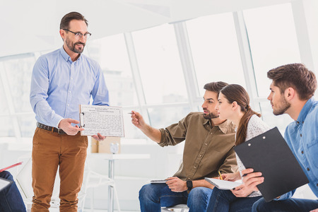 amiable: Amiable man is holding questionnaire. People are looking at it with interest Stock Photo
