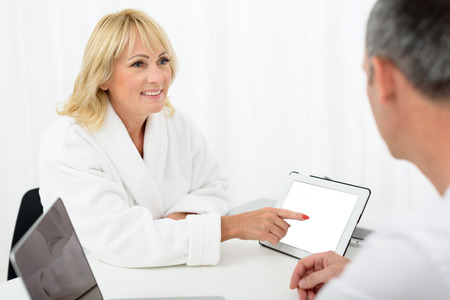 Tell me please about this skincare procedure. Excited mature woman is pointing finger at tablet and looking at cosmetologist with interest. She is sitting at desk in bathrobe and smiling