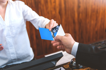 cardkey: This is your pass. Close up of female receptionist giving cardkey to male customer at reception in hotel