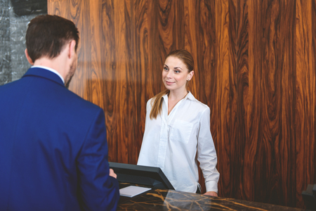 i hope: I hope you enjoy your stay. Friendly female receptionist looking at customer and smiling while standing behind reception desk