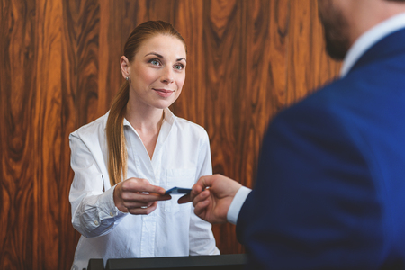 cardkey: This is your pass. Smiling stylish beautiful receptionist handing over cardkey to client at reception desk Stock Photo